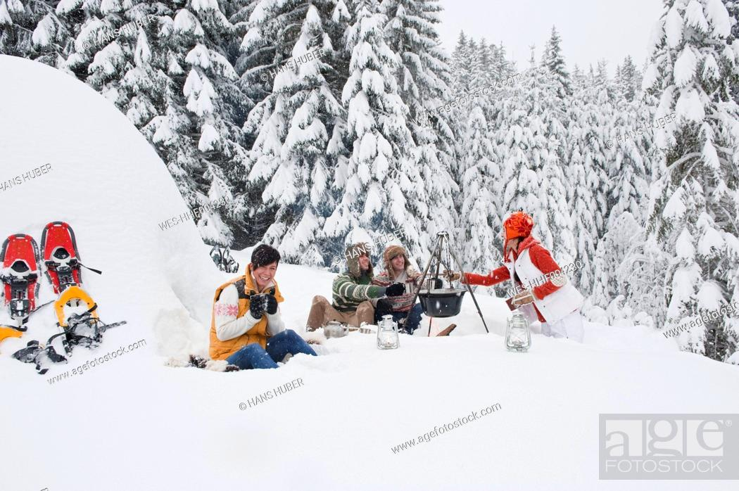 Stock Photo: Austria, Salzburg, Men and women sitting at fire place in winter.
