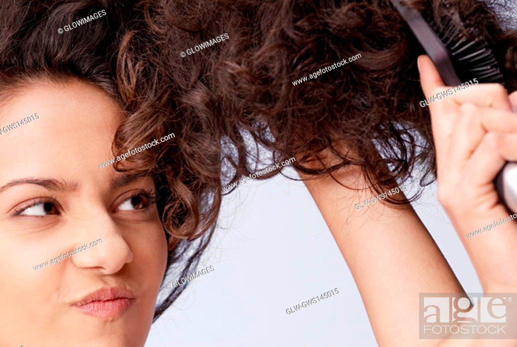 Stock Photo: Close-up of a young woman brushing her hair.