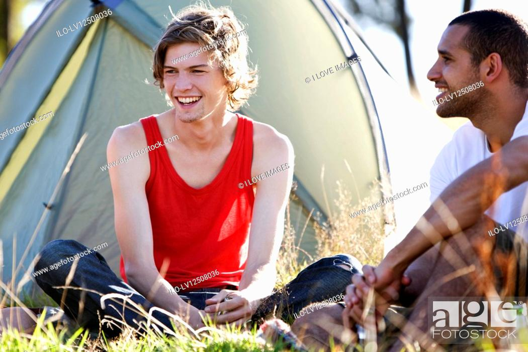 Stock Photo: Two young men sitting in front of a tent, laughing.