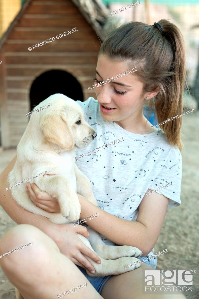 Photo de stock: Portrait of a teenage girl with a golden retriever puppy.