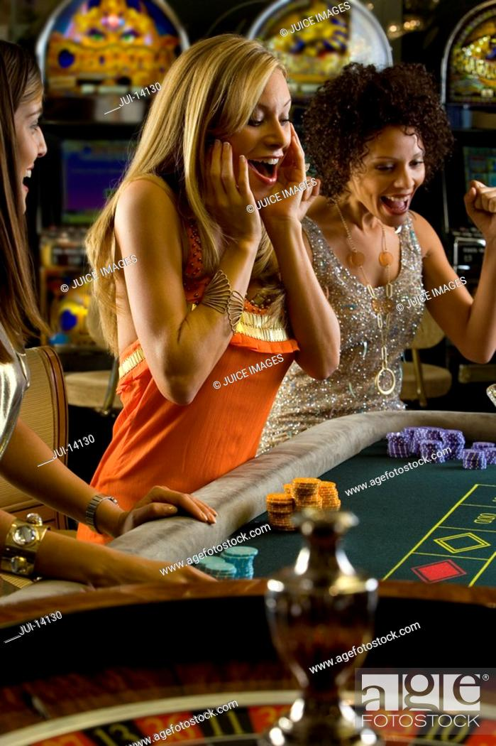 Stock Photo: Young women gambling at roulette table, smiling in celebration.