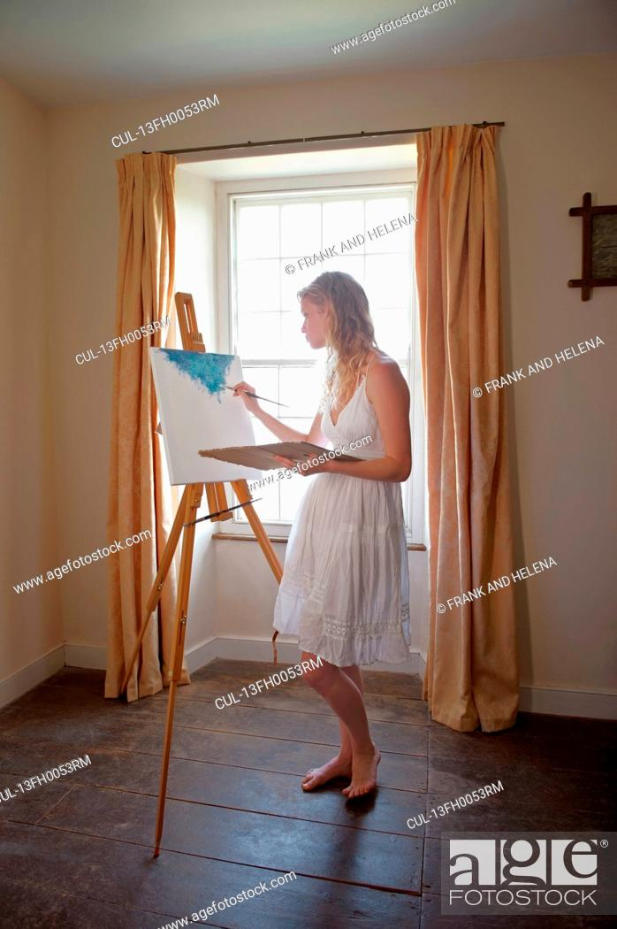 Imagen: Young woman painting by window.