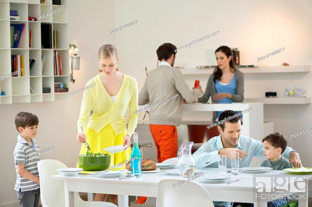 Stock Photo: Family setting table for dinner.
