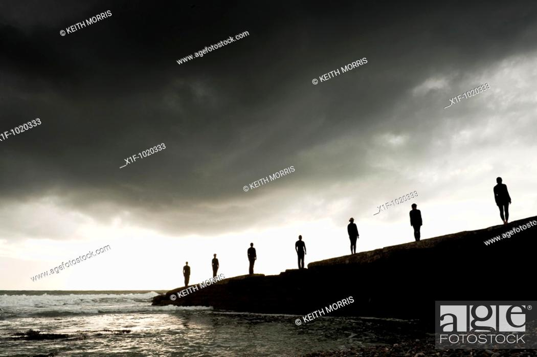 Stock Photo: Silhouettes of 7 people standing on a sea wall.