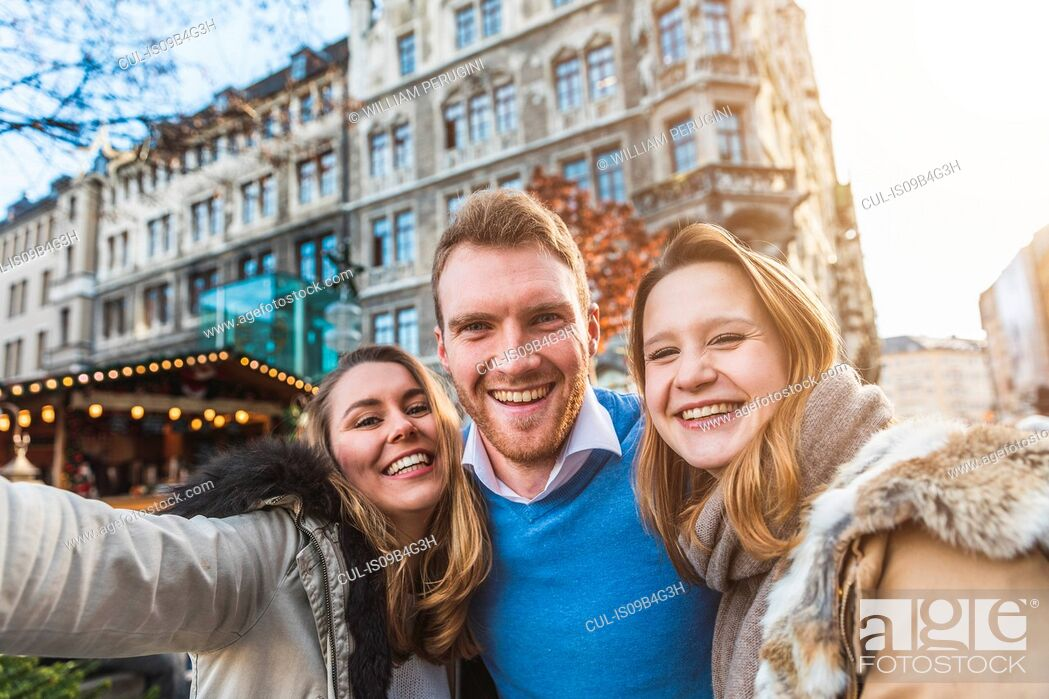 Stock Photo: Portrait of young man and female friends at christmas market.