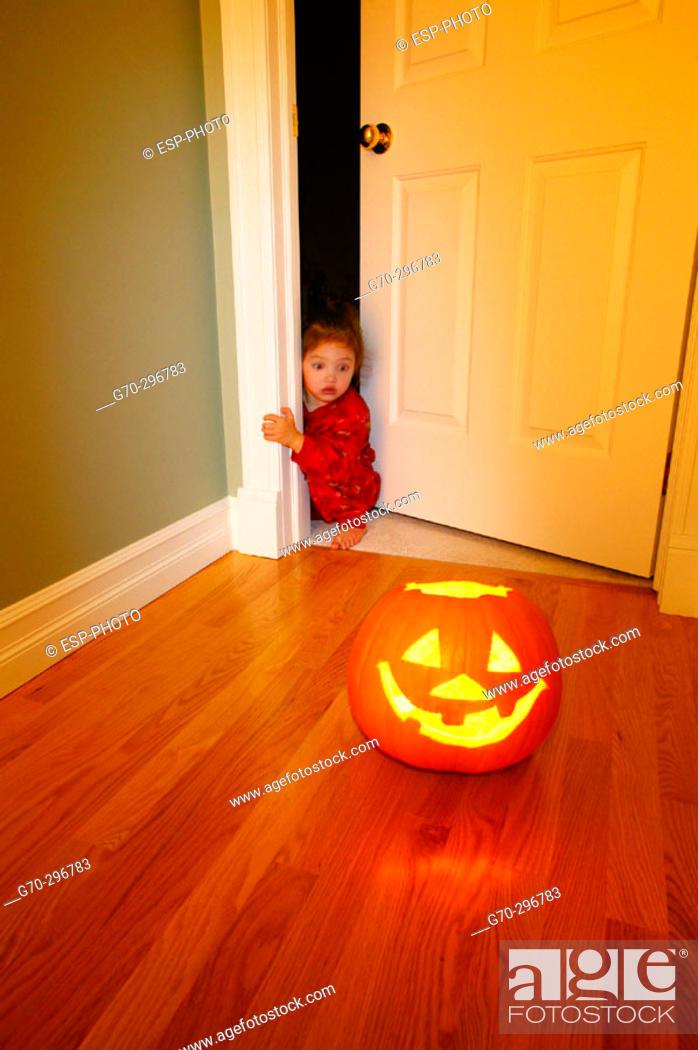 Stock Photo: Halloween Jack-o'-lantern with scared little girl peeking around corner.