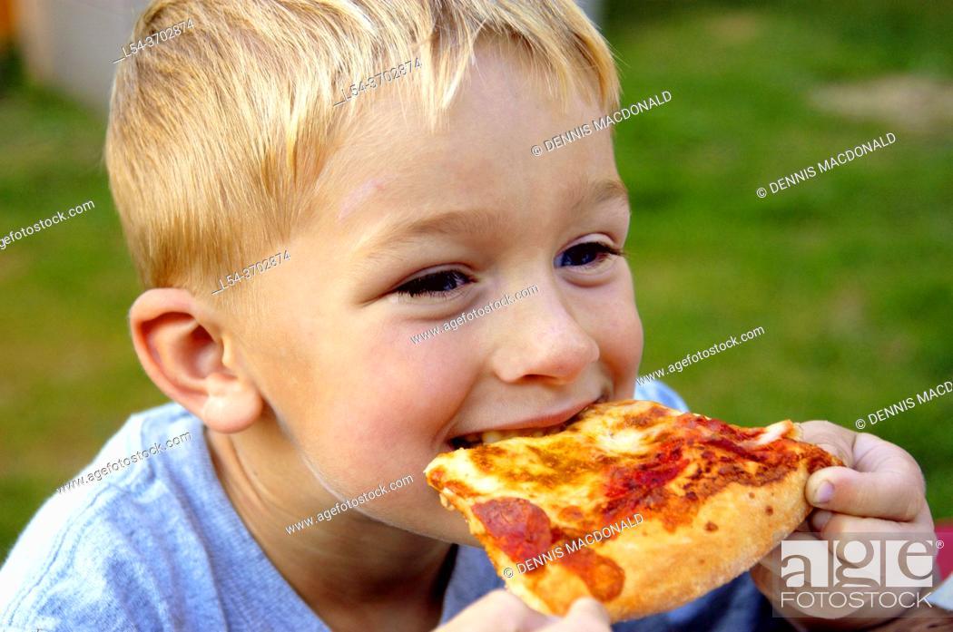 Imagen: Young boy eats pizza at a picnic.