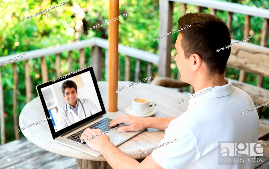 Stock Photo: man having video chat with doctor on laptop.