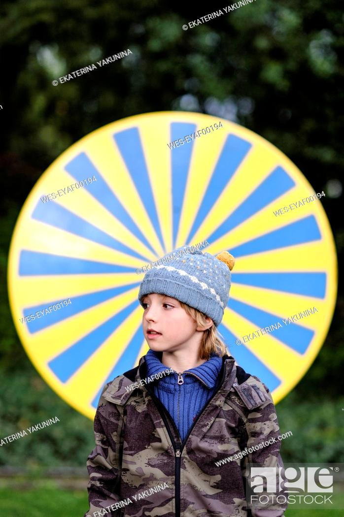Stock Photo: Portrait of boy wearing warm clothing standing in front of yellow and blue circle.