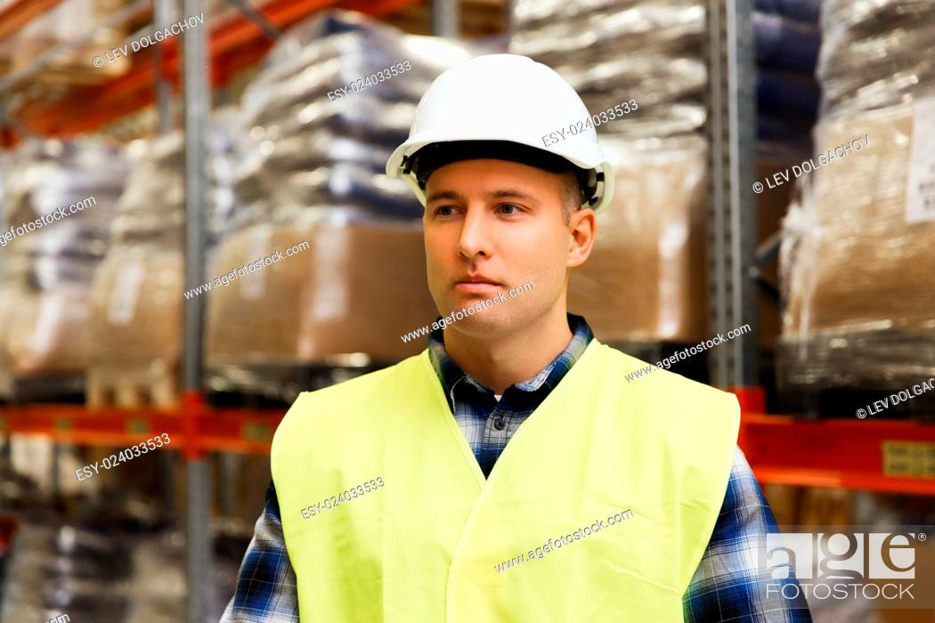 Stock Photo: wholesale, logistic, people and export concept - man in reflective safety vest and hardhat at warehouse.