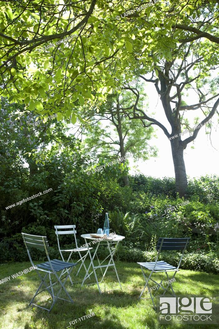 Stock Photo: A table and chairs set up under the shade of a tree.