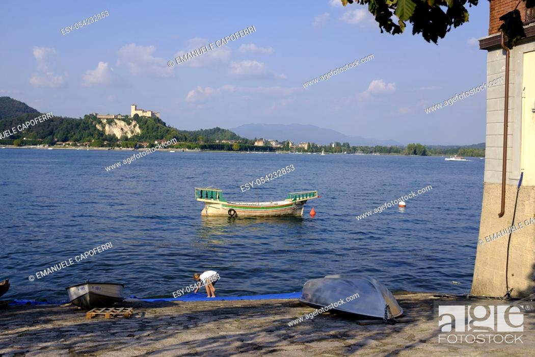 Stock Photo: Reproduction of ancient ship, City Arona, Lake Maggiore, background the fortress of Angera, Piedmont, Italy.