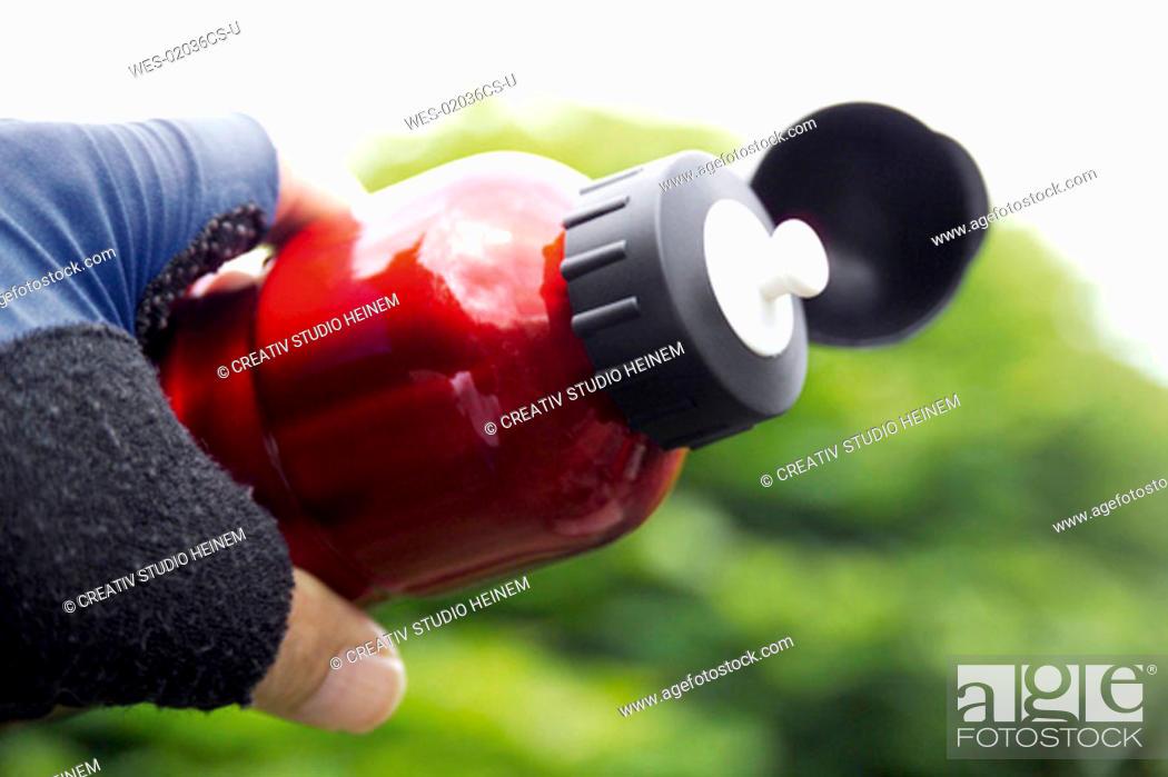 Stock Photo: biker holding drinking-bottle.