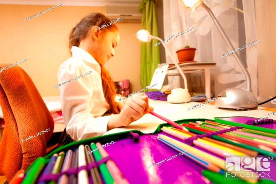 Stock Photo: Little girl taking pencil of pencil-case.