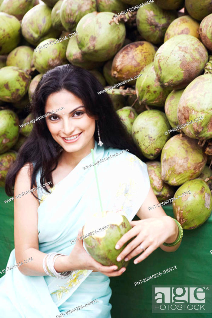 Stock Photo: Portrait of a young woman holding a coconut.