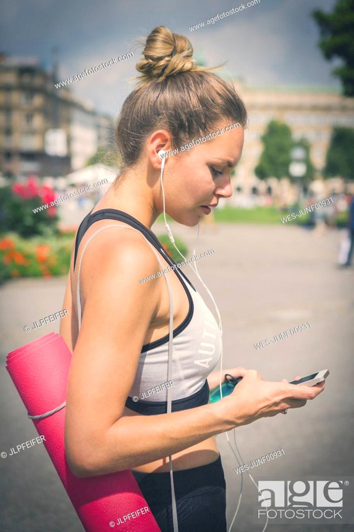 Stock Photo: Young woman with yoga mat, cell phone and earphones in the city.