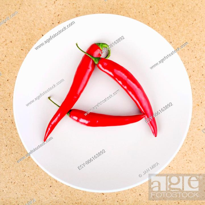 Stock Photo: Fresh raw red hot chili peppers on plate arranged in A letter shape.