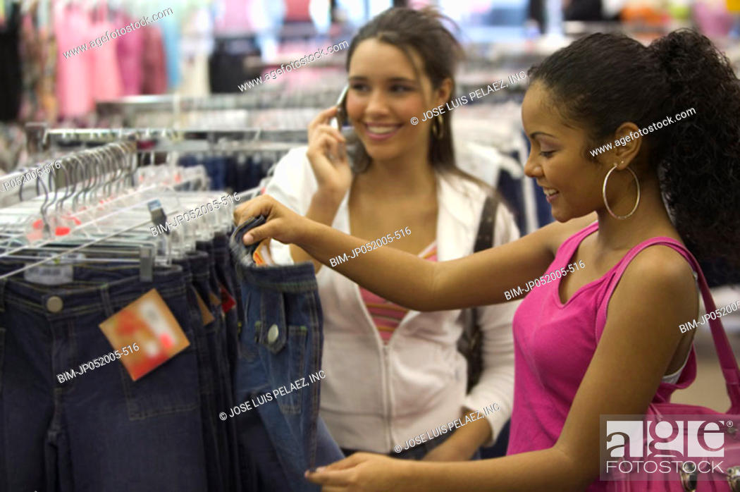 Stock Photo: Two teen girls shopping for clothes.