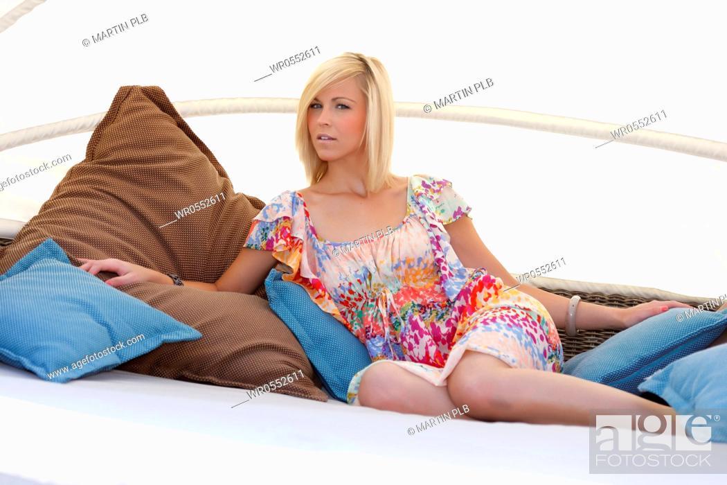 Imagen: beautiful young woman relaxing in garden lounge.