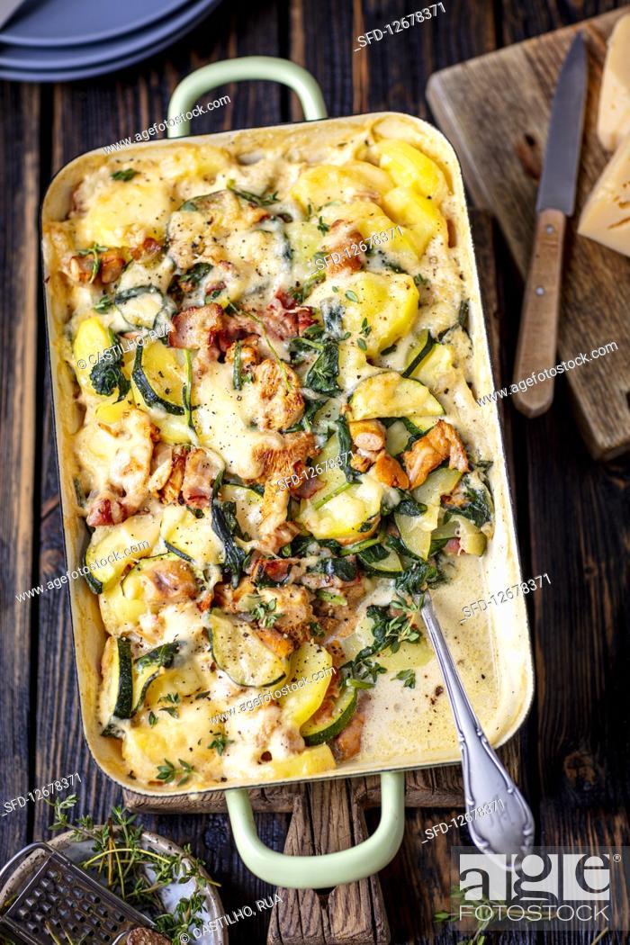 Stock Photo: Potato bake with chanterelles, bacon, courgette and cream.