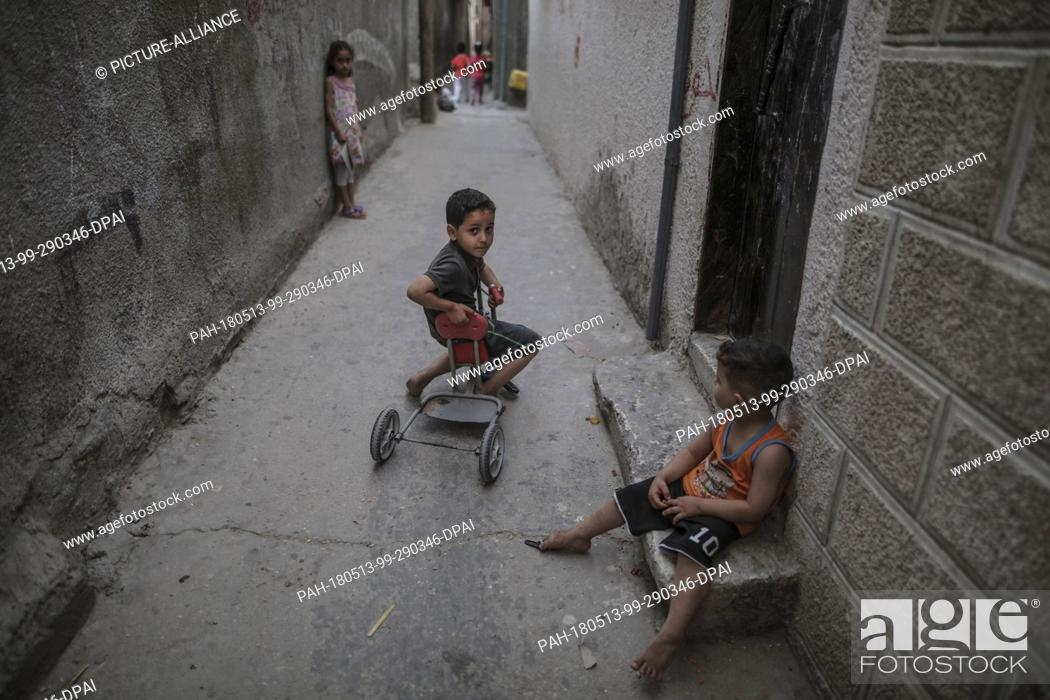 dpatop - A Palestinian refugee children play outside the