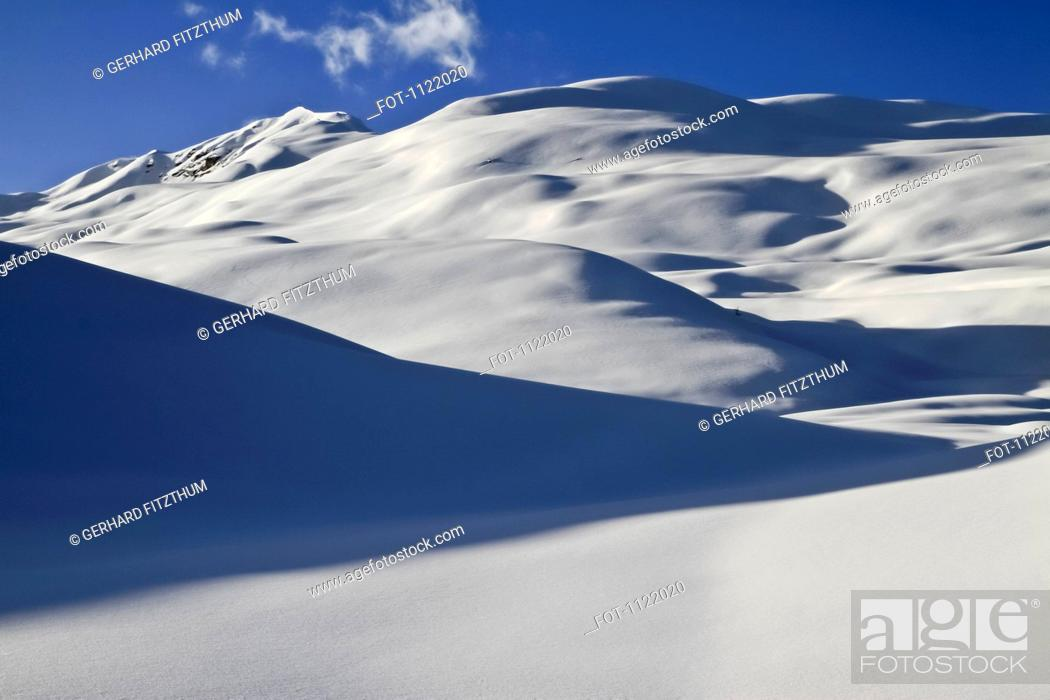 Stock Photo: Smooth blanket of snow over hills.