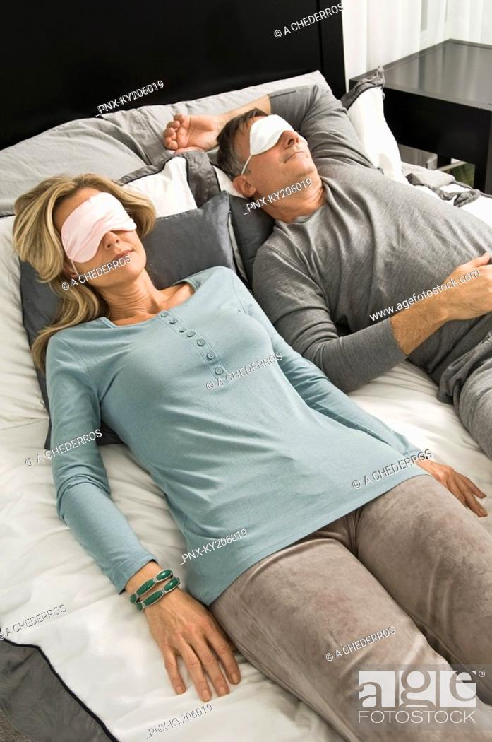 Stock Photo: Couple sleeping in bed wearing eye masks.