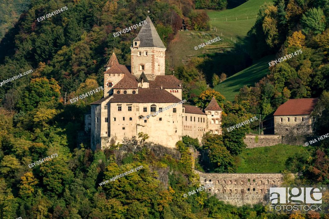 Stock Photo: Waidbruck, South Tyrol, Italy - october 23, 2019: castle Trostburg on a sunny autumn day surrounded by colourful trees.