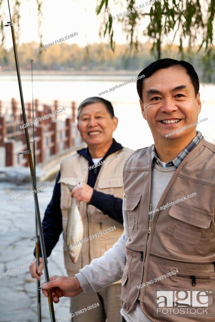 Stock Photo: Senior friends portrait while fishing at a lake.