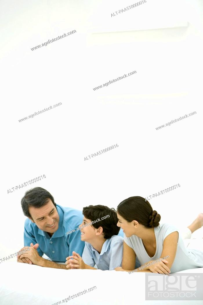Stock Photo: Family lying on bed together, smiling at each other.