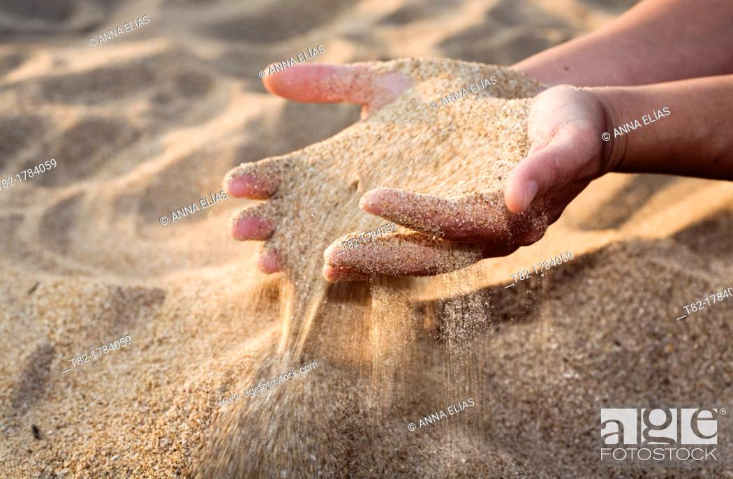 Stock Photo: close-up of woman hands caressing beach sand.