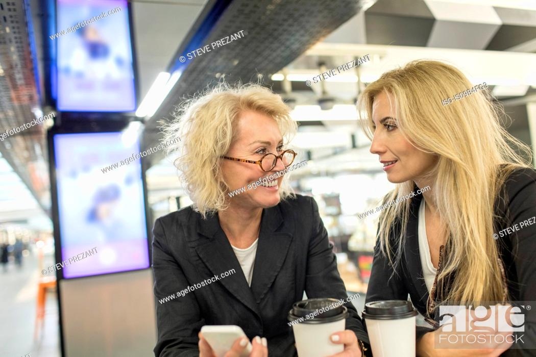 Stock Photo: Two mature female friends chatting in shopping mall cafe.