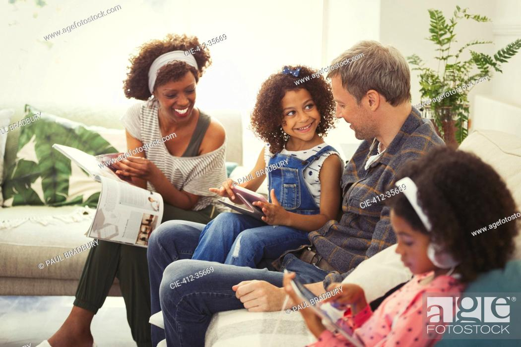 Stock Photo: Multi-ethnic young family using digital tablets and reading magazine on sofa.