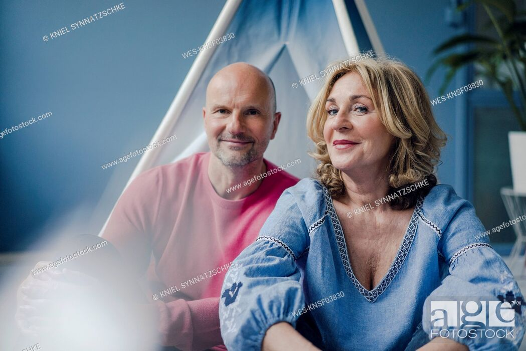 Stock Photo: Portrait of smiling couple at teepee indoors.