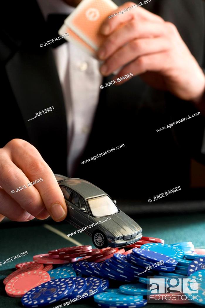 Stock Photo: Man placing model car on pile of gambling chips on table, mid section.
