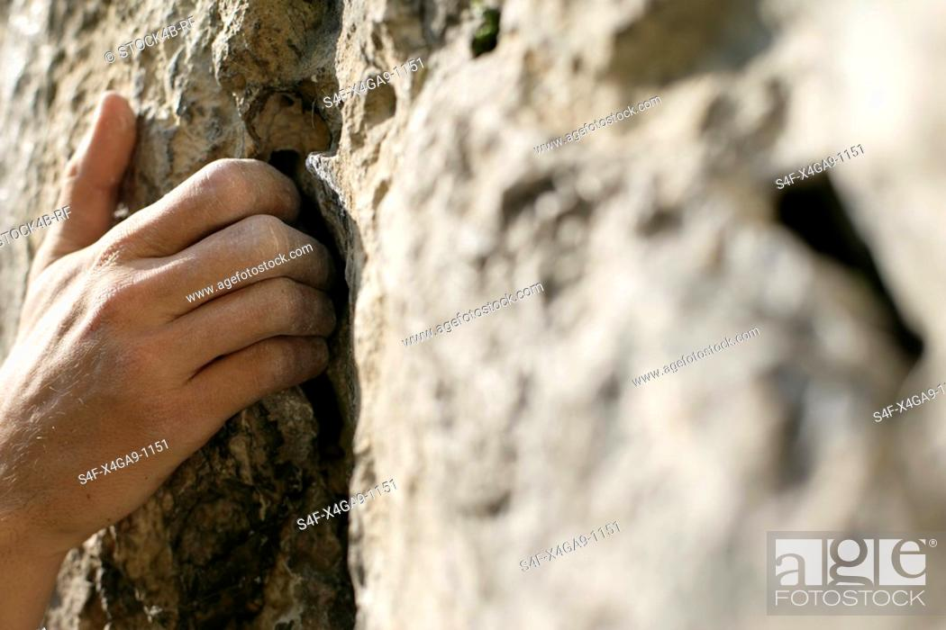 Stock Photo: Dirty male hand touching a rocky wall, close-up, selective focus.
