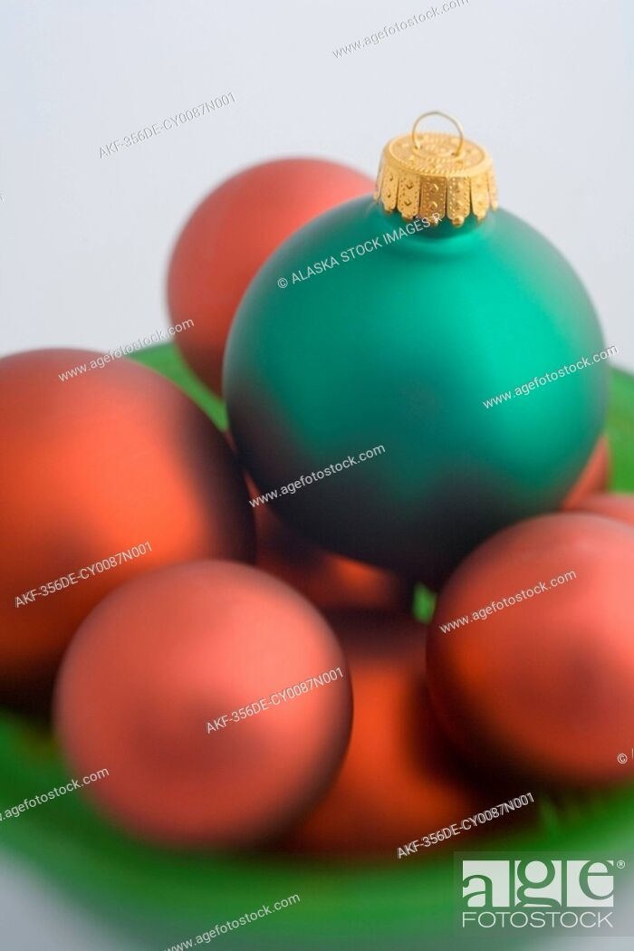 Stock Photo: Green and red Christmas tree bulb ornaments piled in green glass bowl studio portrait.