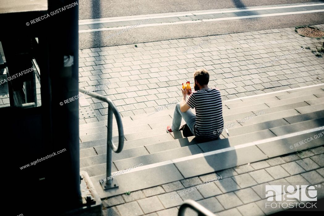 Stock Photo: Rear view of man holding food package while sitting on steps.
