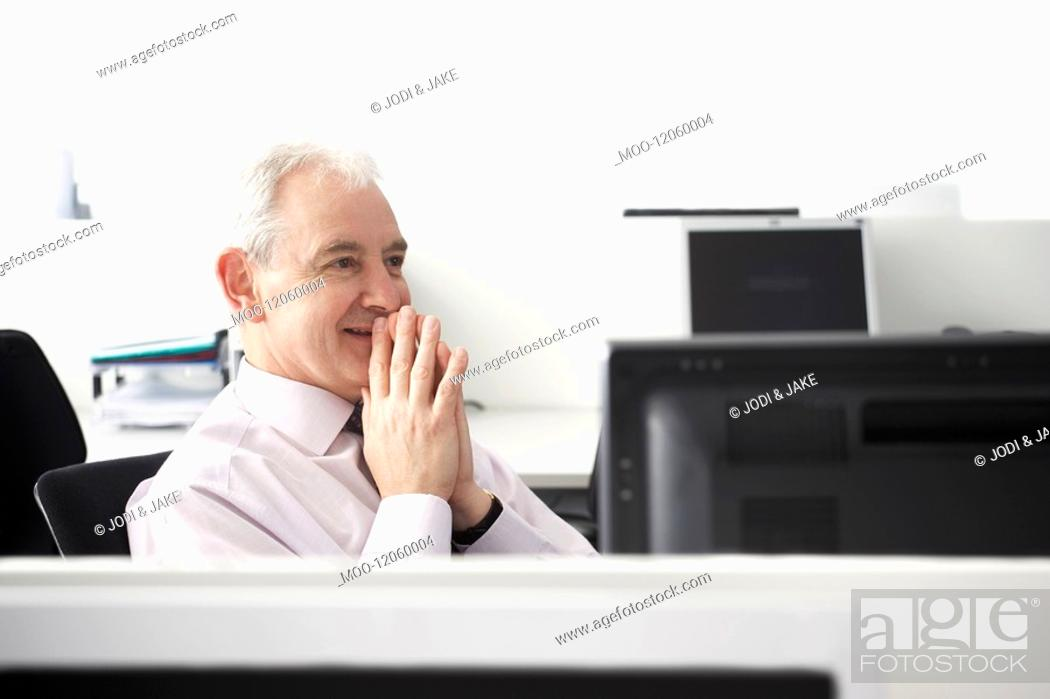 Stock Photo: Mature businessman sitting with folded hands in office cubicle.