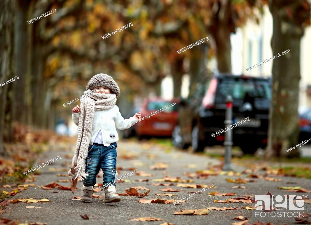Stock Photo: Portrait of happy little girl wearing big scarf and woolly hat in autumn.