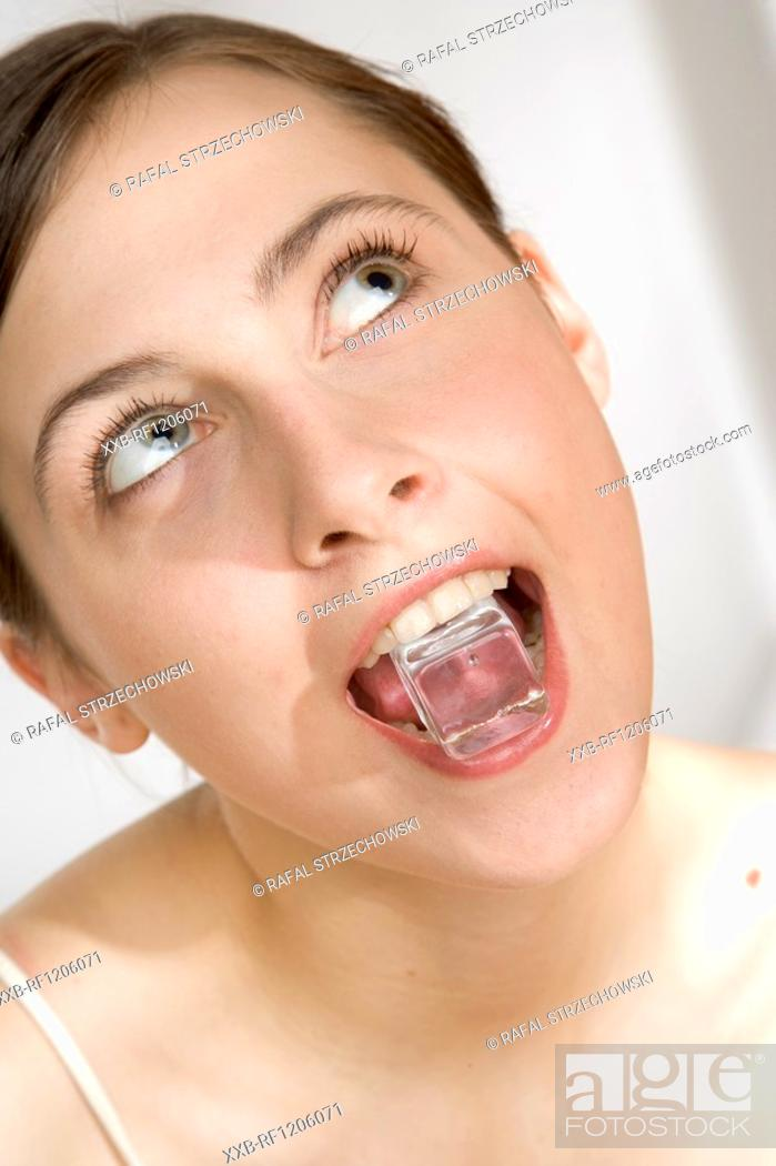 Stock Photo: young woman with ice cube in mouth.