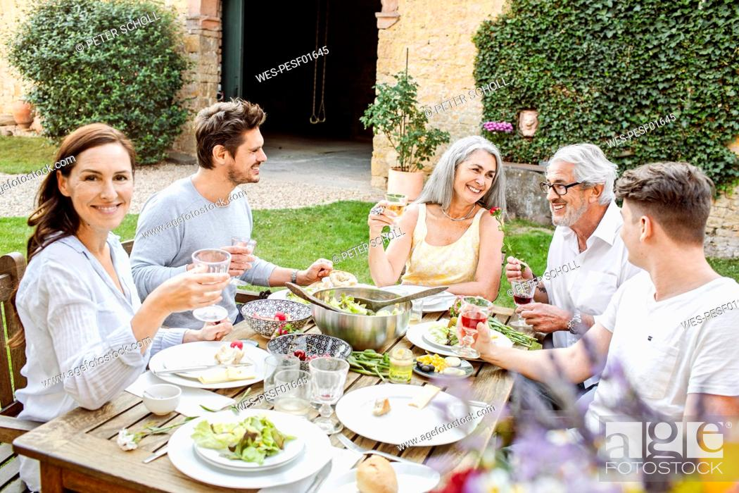 Imagen: Happy family eating together in the garden, clinking glasses.