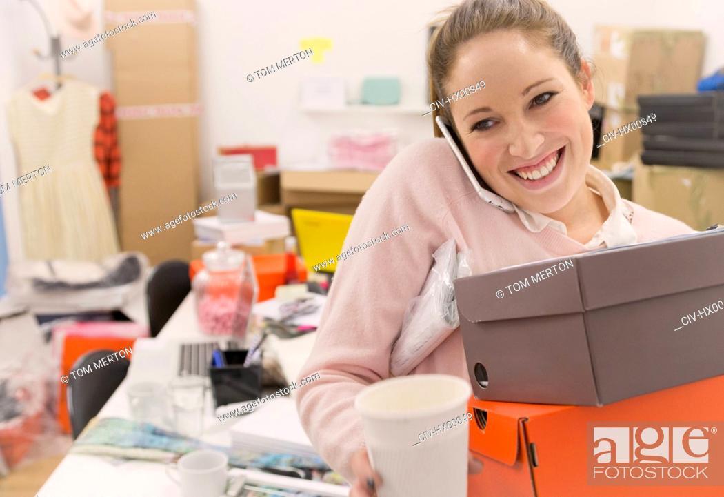 Stock Photo: Smiling fashion buyer multitasking in office.