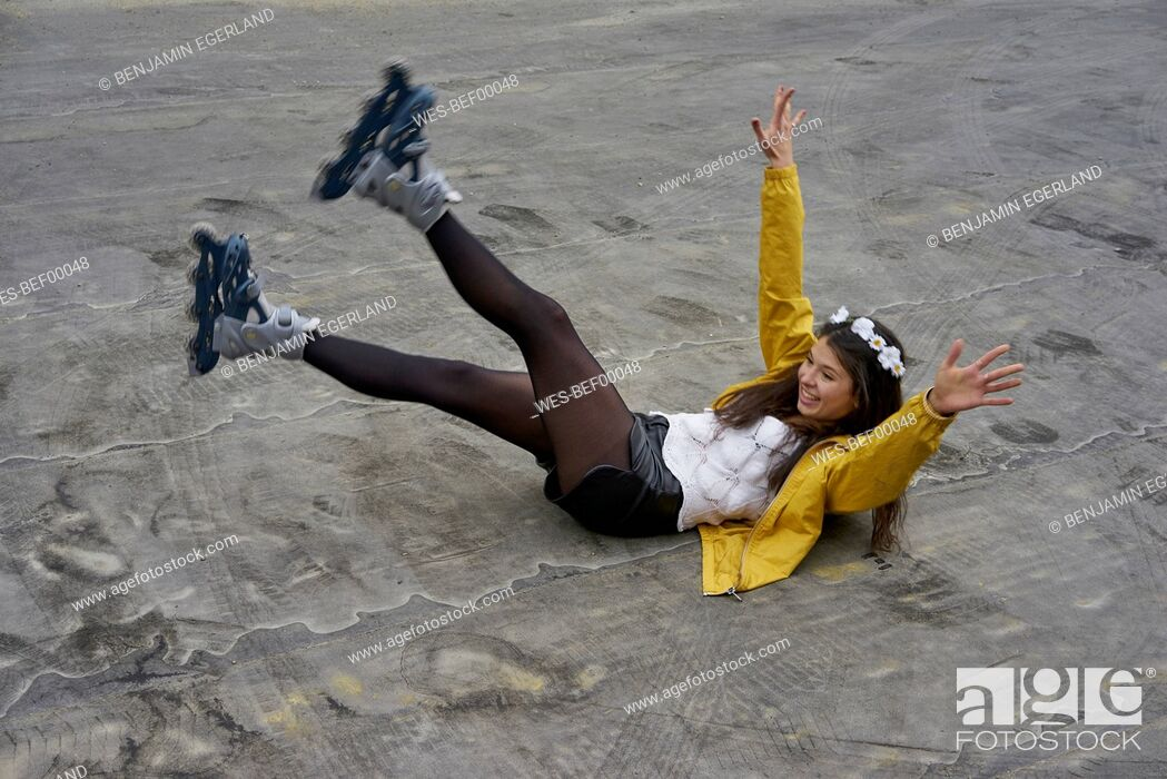 Stock Photo: Smiling woman with inline skates falling on ground.