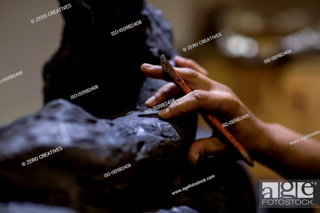 Stock Photo: Cropped view of sculptor in artists' studio creating sculpture with hand tool.