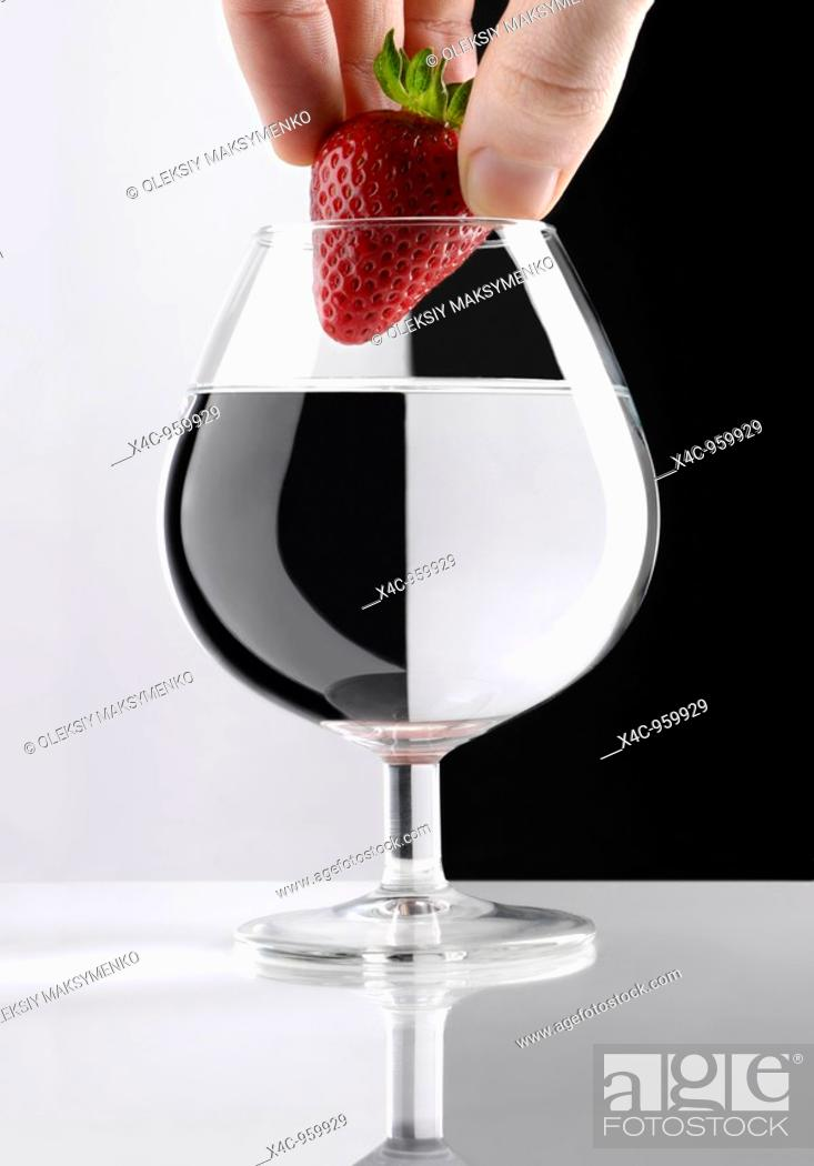 Stock Photo: Hand with a red strawberry over a glass of clear liquid divided into two parts with a refraction effect Artistic concept.