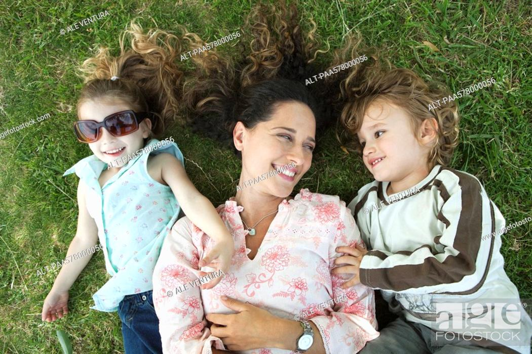 Stock Photo: Mother lying on grass with young children.