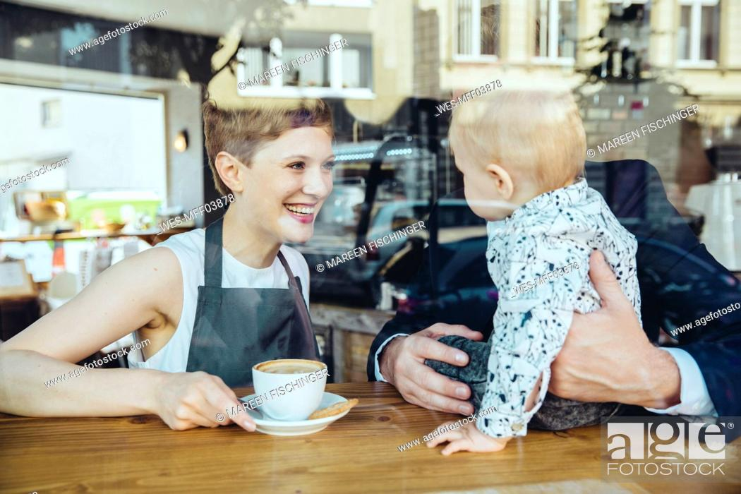 Stock Photo: Waitress serving coffee to smiling customer with baby in cafe.