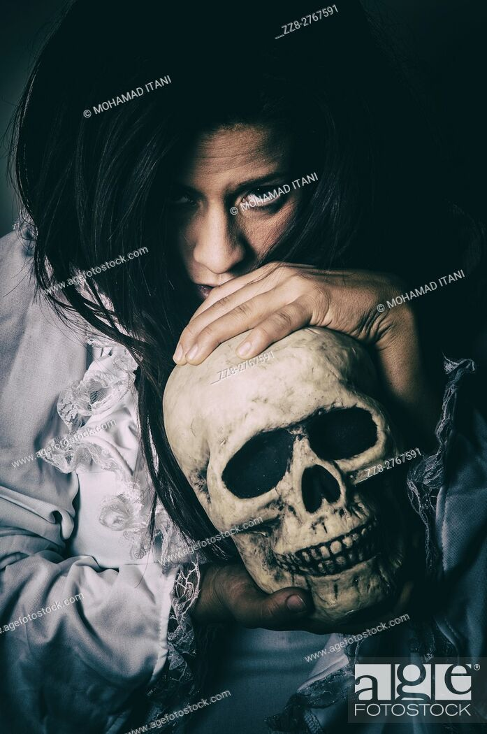 Stock Photo: Frightened woman holding a skull.