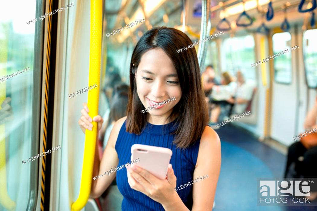 Stock Photo: Woman using mobile phone in train.
